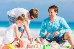 Father with kids at beach. Father and kids playing with sand on beach while enjoying summer vacation stock photography
