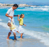 Father with kids on beach Stock Images