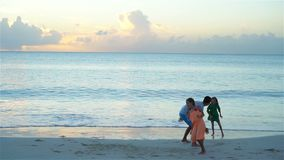 Family enjoying beach time at sunset. SLOW MOTION. Father and kids enjoying beach summer vacation stock footage