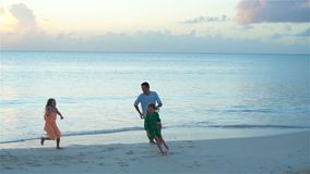Happy father with kids play on beach. Happy family having fun during summer beach vacation. Father and kids enjoying beach summer vacation stock video footage