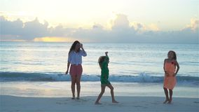 Mother and kids enjoying beach summer tropical vacation. Family dancing on white beach. SLOW MOTION stock video footage