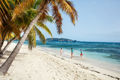 Father with kids at beach. Father and kids enjoying beach vacation on tropical island stock image