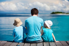 Father and kids enjoying ocean view. Back view of father and kids sitting on wooden dock looking to ocean Royalty Free Stock Image