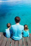 Father and kids enjoying ocean view. Back view of father and kids sitting on wooden dock looking to ocean Royalty Free Stock Images