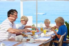 Father with kids having breakfast in resort restaurant. Happy family of four, father with three kids, enjoying summer vacation eating healthy breakfast in the royalty free stock images