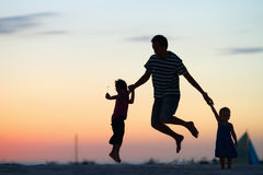 Father and kids jumping at sunset. Silhouettes of father and his two kids jumping and having fun on beach at sunset royalty free stock photo
