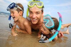 Father and kids laying on the beach Stock Photography