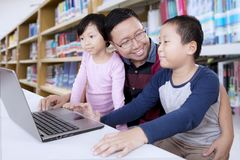 Father and kids learning online together. Father and kids learning online with a laptop computer together in a library Royalty Free Stock Image