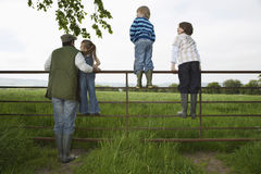 Father With Kids Looking At Lush Landscape By Fence Royalty Free Stock Photos
