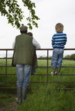 Father With Kids Looking At Lush Landscape By Fence Stock Photography