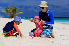 Father and kids making sand castle at tropical beach Stock Photography