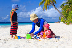 Father and kids making sand castle at tropical Stock Images