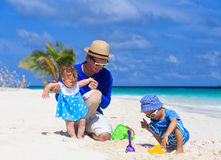 Father and kids making sand castle at tropical Royalty Free Stock Images