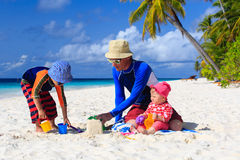 Father and kids making sand castle at tropical Stock Image