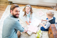 Father and kids packing gifts. Happy young father and two kids sitting on carpet and packing gifts royalty free stock image