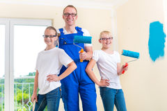 Father and Kids paint a wall in home Stock Photos