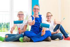 Father and Kids paint a wall in home Stock Images