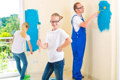 Father and Kids paint a wall in home Royalty Free Stock Photos