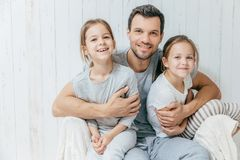 Father and kids. Paternity concept. Handsome unshaven affectionate dad embraces his two pretty dauhters, going to have walk. Together, have good relationship stock image