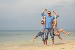 Father and children playing on the beach at the day time. Royalty Free Stock Photo