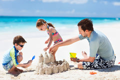 Father and kids playing at beach Stock Photos