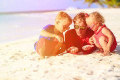 Father and kids playing with sand on beach. Family vacation Royalty Free Stock Images