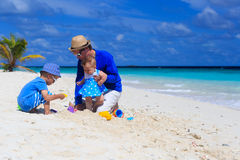 Father and kids playing at sand beach. Father and kids playing at tropical sand beach Royalty Free Stock Image