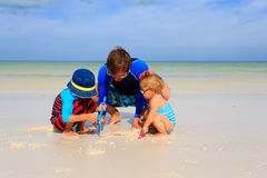 Father and  kids playing with sand on summer beach. Father and two kids playing with sand on summer tropical beach Royalty Free Stock Images