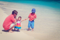 Father and kids playing on sea vacation stock photos