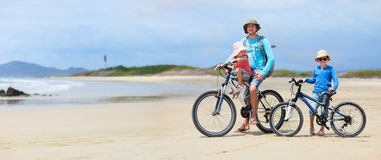 Father and kids riding bikes Royalty Free Stock Images