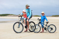 Father and kids riding bikes Stock Photos
