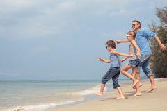 Father and children playing on the beach at the day time. Royalty Free Stock Images
