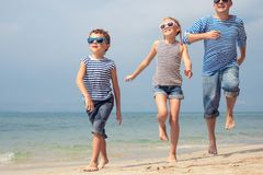 Father and kids running on the beach at the day time. Royalty Free Stock Photos