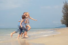 Father and children playing on the beach at the day time. Royalty Free Stock Photography