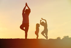 Father with kids silhouettes doing yoga at sunset. Sky royalty free stock photos