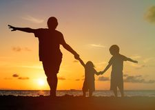 Father with kids silhouettes having fun at sunset. Beach royalty free stock photos