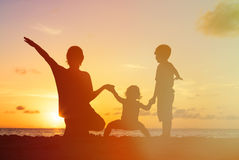 Father with kids silhouettes having fun at sunset. Beach royalty free stock image