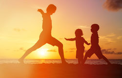 Father with kids silhouettes having fun at sunset. Beach stock photography