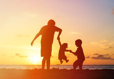 Father with kids silhouettes having fun at sunset Royalty Free Stock Photo