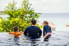 Father and kids at swimming pool. Happy family father and his kids at outdoors infinity swimming pool enjoying views royalty free stock images