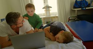 Father and kids using laptop on bed 4k. Father and kids using laptop on bed at home 4k stock video