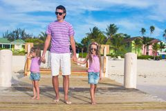 Father and kids walking on wooden dock during Royalty Free Stock Images