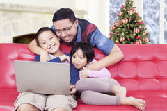 Father and kids watching movie on laptop Royalty Free Stock Images