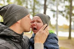 Father kiss crying child whom holds on hands Royalty Free Stock Photography