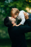 Father kiss his son. In arms stock image