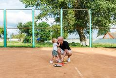 The father kisses the daughter before a playing in tennis stock photo