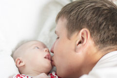 Father kisses his newborn son. Young caucasian men kisses  his little newborn son lying on cradle Stock Images