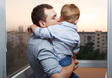 Father kisses his son on the balcony. Thirty year old father kisses his three year old son on the balcony Stock Photography
