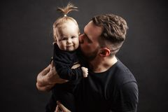Father kissing adorable baby. Loving father kissing his little baby daughter holding her on hands at studio black background with copyspace. Family Relations Stock Images