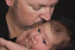 Father kissing baby daughter. Portrait of father cradling and kissing baby daughter, black background Stock Images